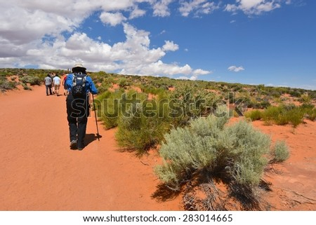 PAGE, AZ - MAY 26: Hikers at Horseshoe Bend on May 26, 2015 in Page AZ,USA. Thousands of people from all over the world come to visit this beautiful place every year. - stock photo