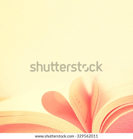 page book in curved heart shape in blur style background - stock photo