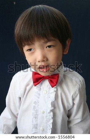 page boy with red bow-tie, wondering face expression. - stock photo