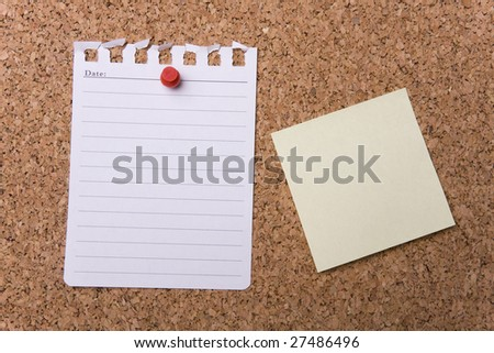 Page from a notepad stuck to a cork noticeboard - stock photo