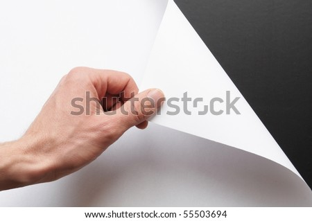page or blank sheet of paper with hand and copyspace in the corner - stock photo