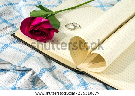 Pages of a book curved into a heart shape and red roses. Valentines day - stock photo