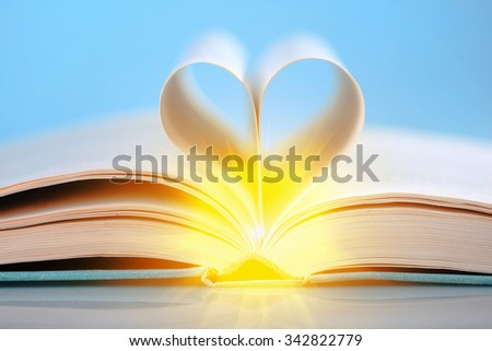 Pages of a book curved into a heart shape on blue background - stock photo
