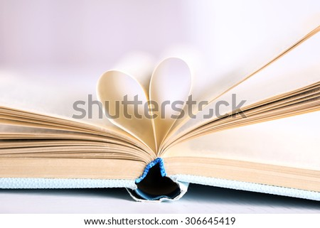 Pages of book curved into heart shape, close up - stock photo