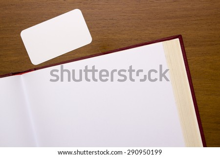 Pages of the book open to a blank page with a clear card. - stock photo