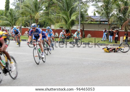 PAHANG, MALAYSIA - MARCH 1: An unidentified cyclist falls, one of several cyclists from various teams that fell on this corner, during Stage 7 of the Tour de Langkawi from Bentong to Kuantan on March 1, 2012 in Pahang, Malaysia. - stock photo