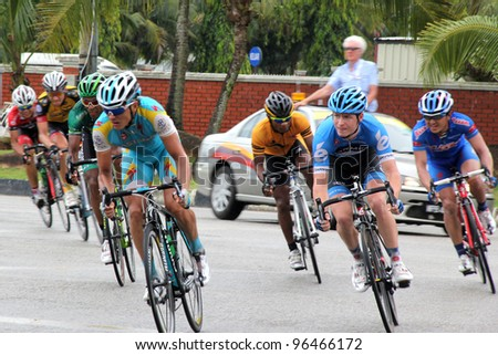 PAHANG ,MALAYSIA - MARCH 1 : The largest group of cyclists from various teams cycle round a corner during Stage 7 of the Tour de Langkawi from Bentong to Kuantan on March 1, 2012 in Pahang, Malaysia. - stock photo