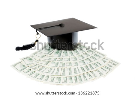 Paid education. Graduate cap on bank notes - stock photo