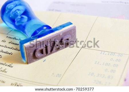 paid letter on rubber stamp with business cash receipt paper background - stock photo