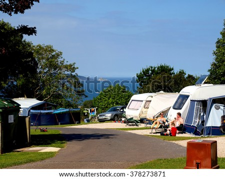 PAIGNTON, DEVON, UK. JULY 22, 2008.  Campers relax at a caravan site overlooking Torbay at Paignton in Devon, UK..