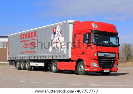 PAIMIO, FINLAND - APRIL 16, 2016: Red, new DAF XF Euro 6 semi truck and curtainsider trailer of Starek Transport parked at a truck stop in South of Finland on sunny day. - stock photo