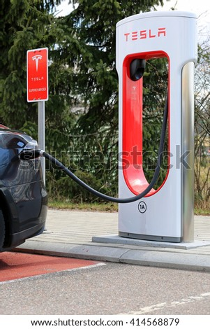 PAIMIO, FINLAND - APRIL 29, 2016: Tesla Supercharger Station with black Tesla Model S electric vehicle being charged. Charging the battery from 10 to 80 percent takes about 40 minutes. - stock photo
