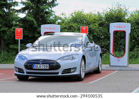 PAIMIO, FINLAND - JULY 5, 2015: Tesla Model S being charged at Tesla Supercharger station. Charging the battery from 10 to 80 percent takes about 40 minutes. - stock photo