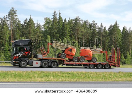 PAIMIO, FINLAND - JUNE 3, 2016: Black Scania truck transports two aerial work platforms on lowboy trailer along freeway in South of Finland.  - stock photo