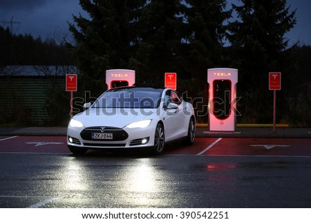 PAIMIO, FINLAND - NOVEMBER 14, 2015: Tesla Model S electric car arrives at the Paimio Tesla Supercharger station at night for charging. Tesla Supercharging stations are open any time. - stock photo