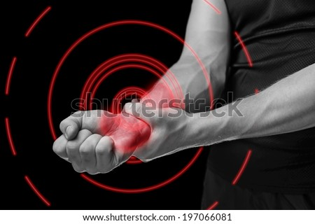 Pain in a male wrist. Man holds his hand, monochrome image, pain area of red color - stock photo