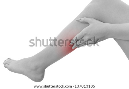 Pain in a woman calf. Female holding hand to spot of  calf-aches. Concept photo with Color Enhanced blue skin with read spot indicating location of the pain. Isolation on a white background. - stock photo