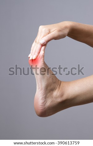 Pain in the foot. Massage of female feet. Pain in the human body on a gray background with red dot - stock photo