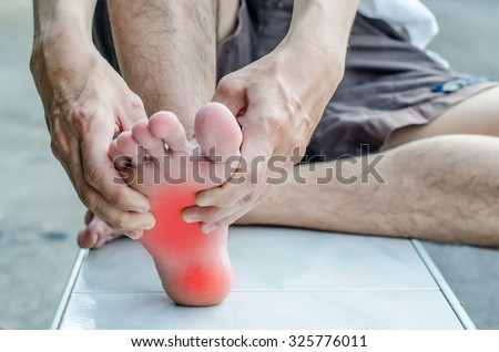 Pain in the foot. Massage of male feet. Pedicures. - stock photo