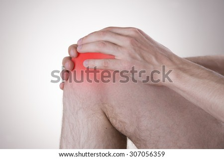 Pain in the knee on a gray background - stock photo