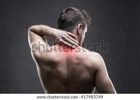 Pain in the neck. Man with backache. Muscular male body. Handsome bodybuilder posing on gray background with red dot - stock photo