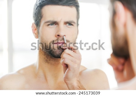 Painful procedure. Concentrated young man tweezing hair from nose and looking at himself while standing in front of the mirror - stock photo