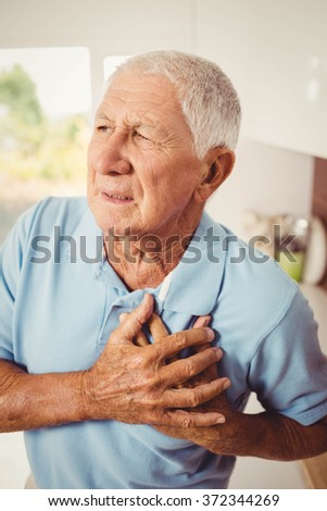 Painful senior man with pain on heart at home - stock photo