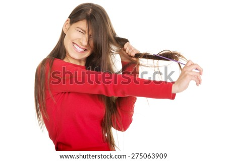 Painful woman combing her tangled hair. - stock photo