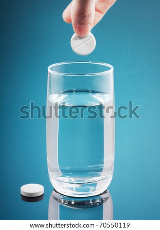 Painkiller tablet in hand over blue background. Vertical. copy-space. - stock photo