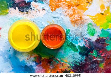 Painring palette and oil pigment, focus on orange pigment - stock photo