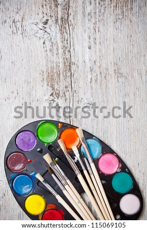 Paint and brushes on wood background - stock photo