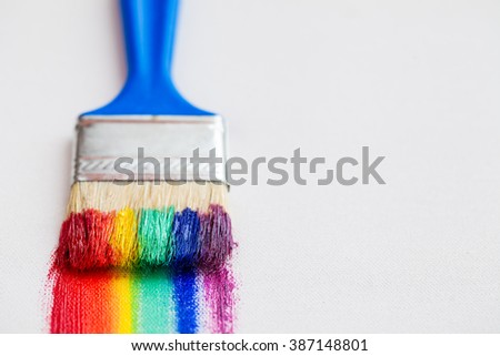 Paint brush closeup and multicolor rainbow brush strokes on white canvas - stock photo