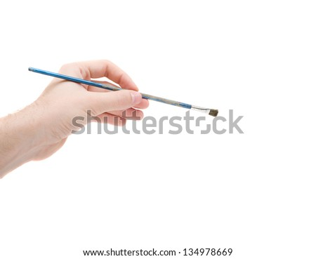 Paint brush in hand of artist isolated on white - stock photo