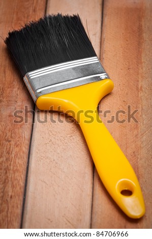 Paint brush on a wooden boards background - stock photo