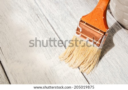 paint brush painting on wooden surface - stock photo