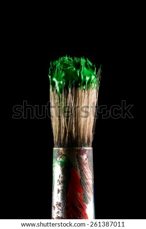 paint brush painting with green color on black background - stock photo