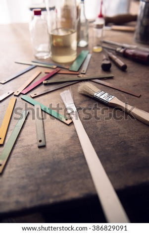 Paint brush, solvents and wood color samples on an old work bench.  Focus is on center  brush metal sleeve. Shallow depth of focus. - stock photo