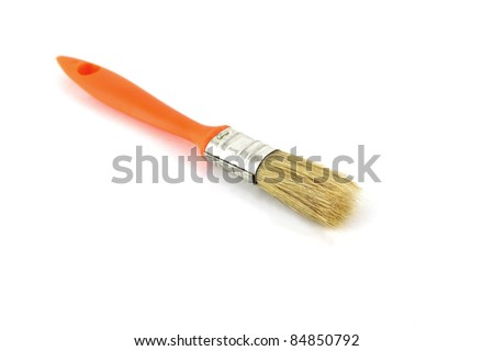 Paint brush with orange handle over white