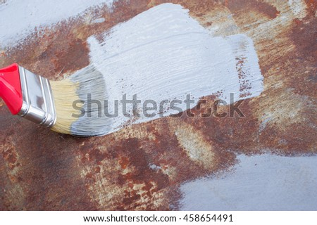 paint brush with paint on the rusty iron