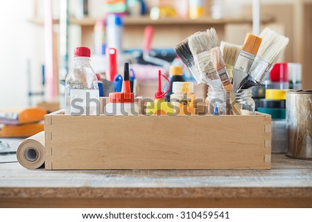 Paint brushes and crafting supplies on the table in a workshop. - stock photo