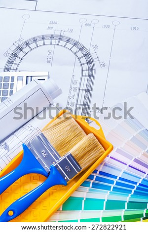 paint brushes and rolls of blueprints  - stock photo