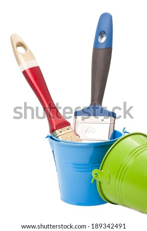 Paint brushes in green and blue tin buckets isolated on white - stock photo