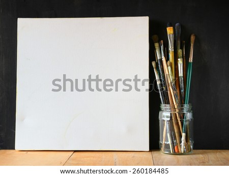 paint brushes in jar and blank canvas over blackboard background  - stock photo