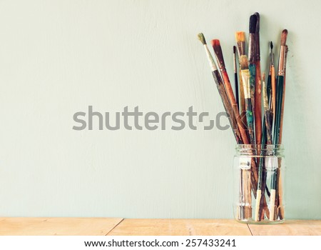 paint brushes in jar over wooden aqua blue background. vintage filtered image - stock photo