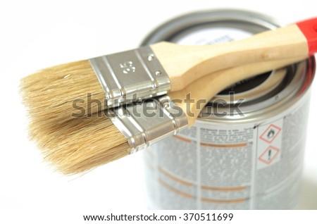 Paint brushes lying on the can of paint on a white background - stock photo