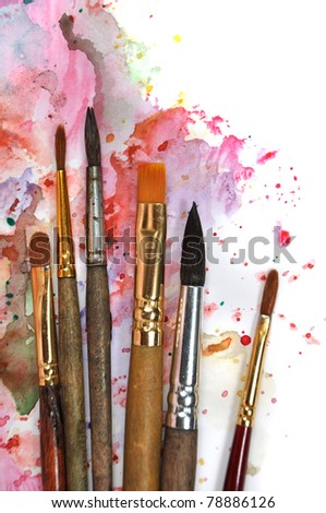 Paint brushes on a watercolor palette - stock photo