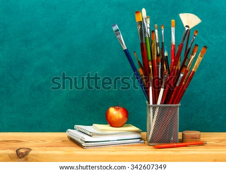 paint brushes on a wooden table - stock photo