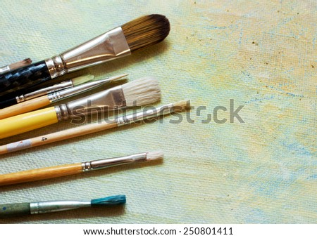 Paint brushes on an oil canvas - stock photo