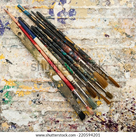 paint brushes on grungy dried paint background  - stock photo