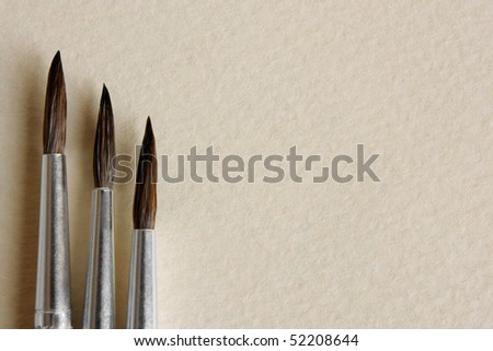 Paint brushes on papers background, a horizontal picture - stock photo